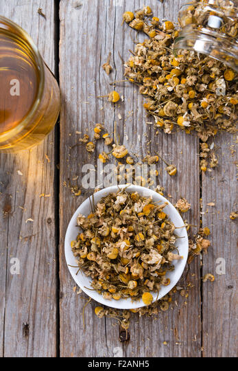 Heap of dried Camomile (close-up shot) on wooden background - Stock Image