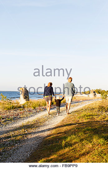 Sweden, Gotland, Farosund, Parents with son (2-3) walking along seaside, rear view - Stock Image