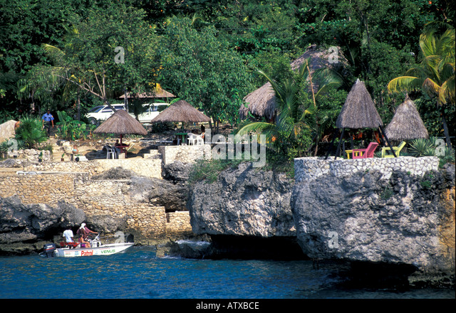 Jamaica Negril Caribbean Thatch Huts overlooking the water - Stock Image