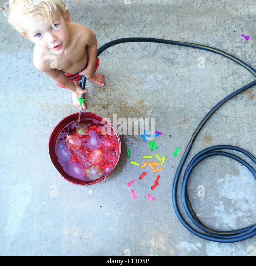 Toddler filling a bucket with water - Stock Image