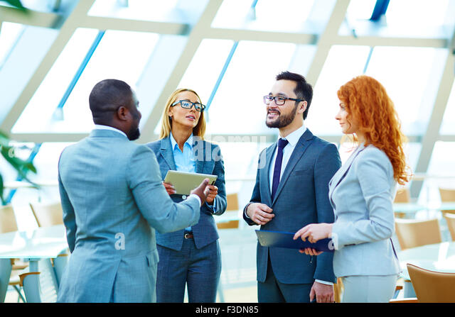 Business co-workers interacting at meeting - Stock Image