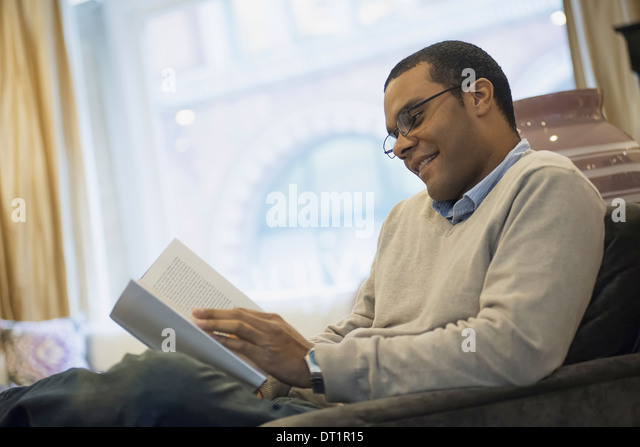 Man relaxing at home reading - Stock Image