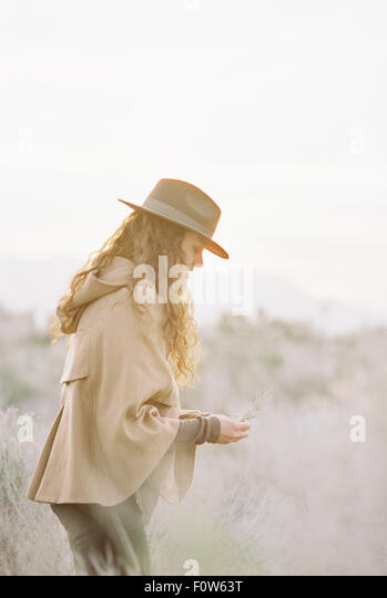 A woman in a warm coat and a hat picking wild flowers. - Stock Image