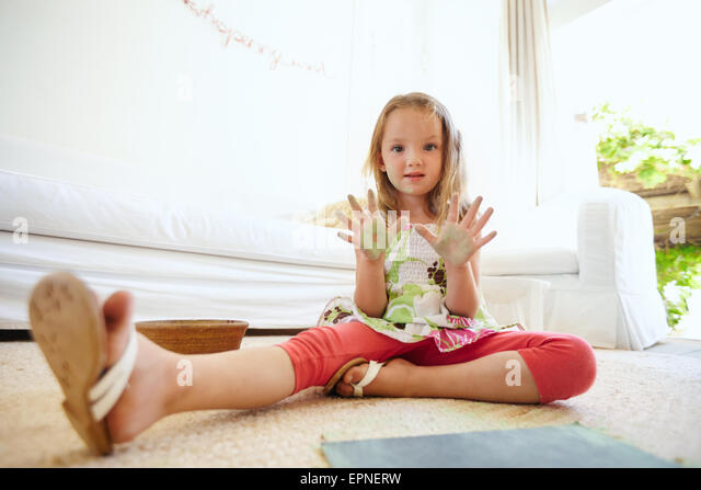 Portrait of beautiful little girl having fun while painting. Schoolgirl sitting on floor at home showing her painted - Stock Image