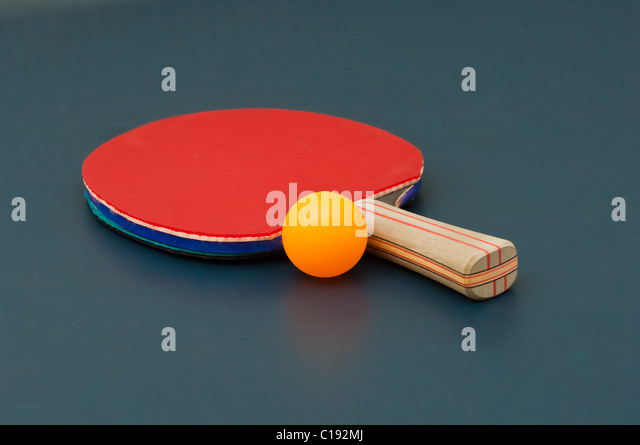 Table tennis rackets and ball on tennis table - Stock Image