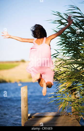 Woman jumping off dock into lake - Stock Image
