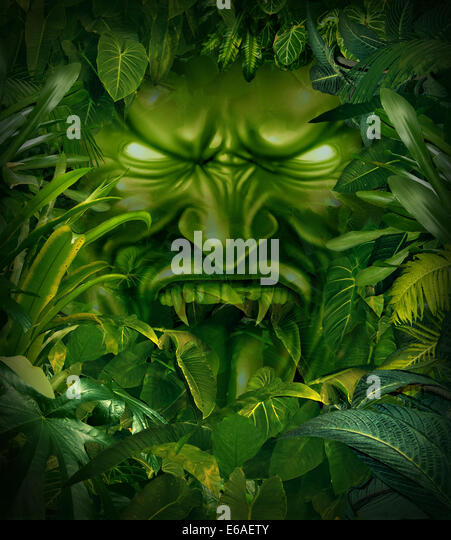 Jungle fear nightmare concept as a scary monster head emerging out from a dark tropical rain forest as a symbol - Stock-Bilder