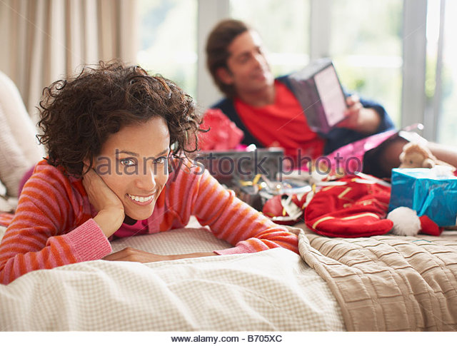 Couple laying on bed with Christmas gifts - Stock Image