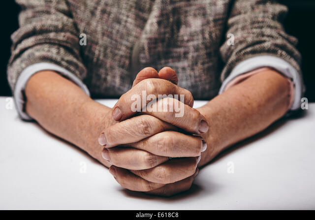 Studio photography of praying hands of a senior woman on table. Old hands clasped on a table. - Stock Image