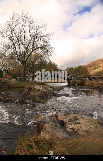 Slater Bridge crosses the River Brathay on its way from Little Langdale Tarn - Stock Image