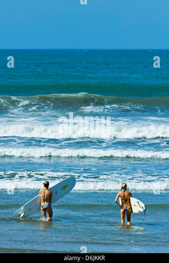 Girls surfing at popular Playa Guiones beach, Nosara, Nicoya Peninsula, Guanacaste Province, Costa Rica, Central - Stock Image