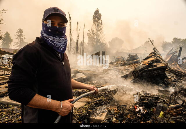 Santa Rosa, California, USA. 9th Oct, 2017. A man hoses down his neighbors home after an overnight wildfire destroyed - Stock Image