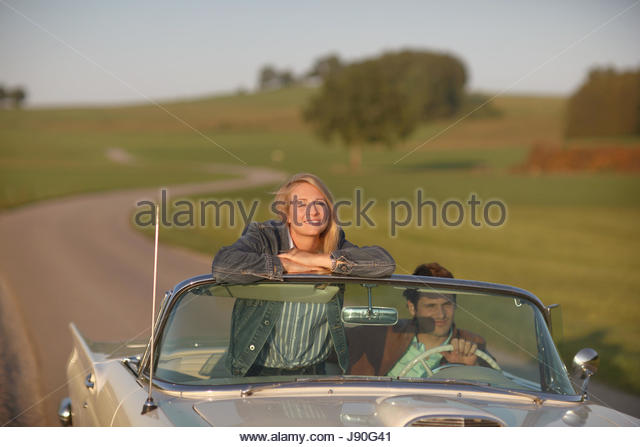 Couple Driving On Country Road In Open Top Classic Car - Stock-Bilder