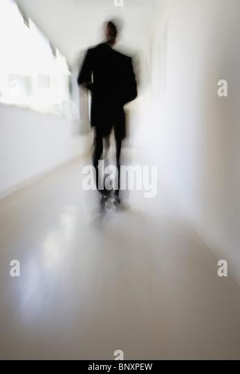 Figure walking down corridor - Stock-Bilder