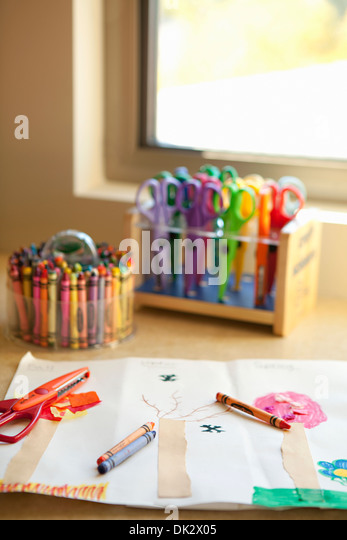 Child's art crayons and scissors at drawing near window - Stock Image