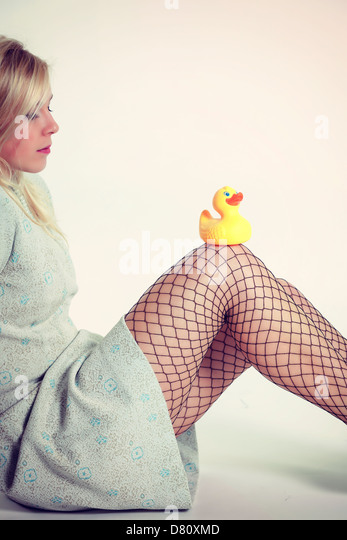 a blond girl with a turqouise dress is sitting with a rubber duck on her knees - Stock Image