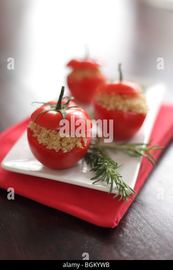 Quinoa stuffed tomatoes with rosemary herb - Stock Image