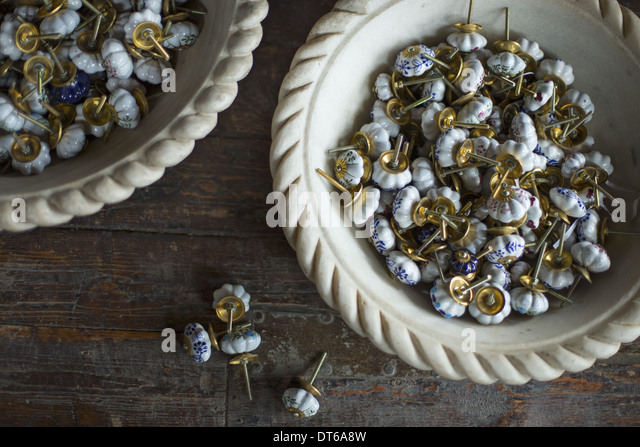 An antique store with objects and furniture from the past. Furniture tacks with ceramic blue and white heads. - Stock Image