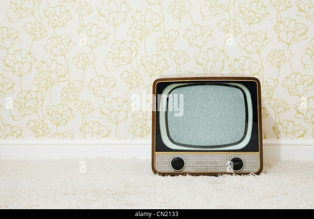 Retro television in room with patterned wallpaper - Stock Image