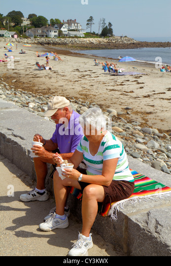 New Hampshire North Hampton North Hampton State Beach Route 1A Atlantic Ocean sand senior man woman couple eating - Stock Image
