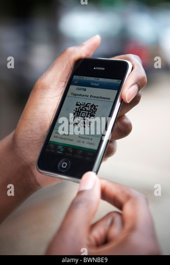 woman holding iphone being used as electronic ticket for railway travel - Stock-Bilder