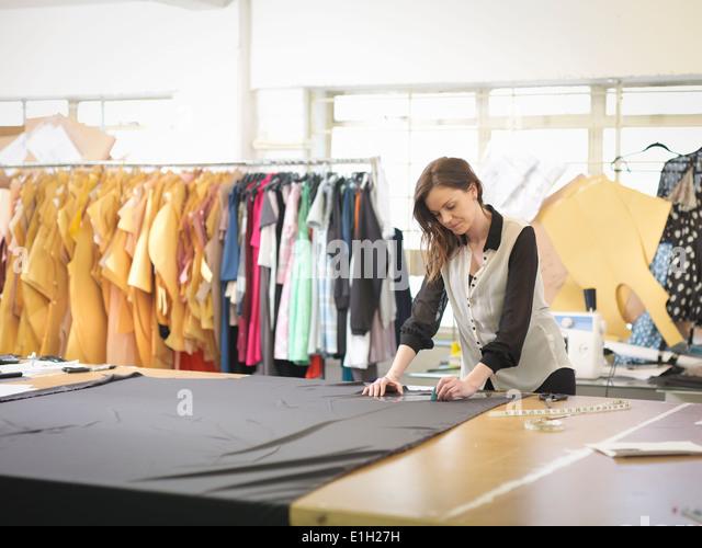 Fashion designer measuring fabric in fashion design studio - Stock Image