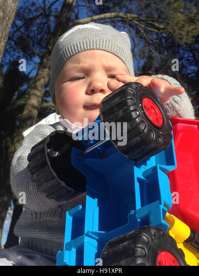 Baby boy playing with dump truck in the park a sunny winter morning - Stock Image