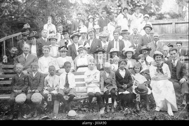Full length landscape shot of adults and children, some seated on a bench, others standing, outdoors, all dressed - Stock Image