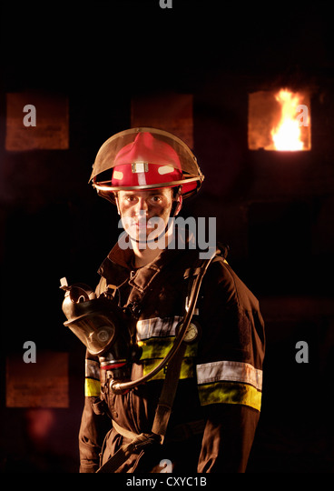 Firefighter in front of a burning building - Stock Image
