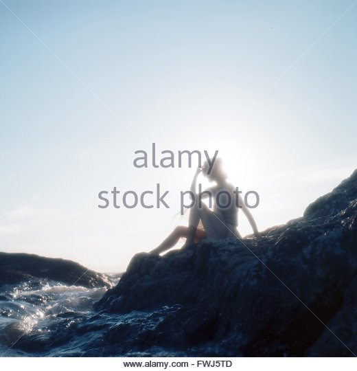 Side View Of A Silhouette Woman Sitting On Beach - Stock Image