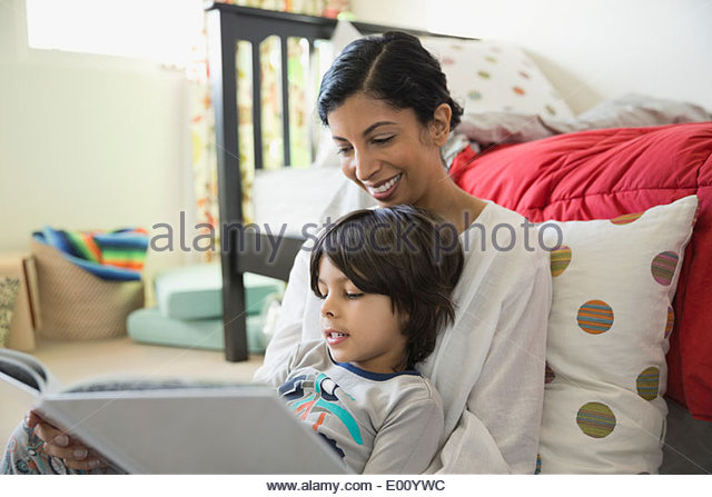 Mother and son reading book in bedroom - Stock Image