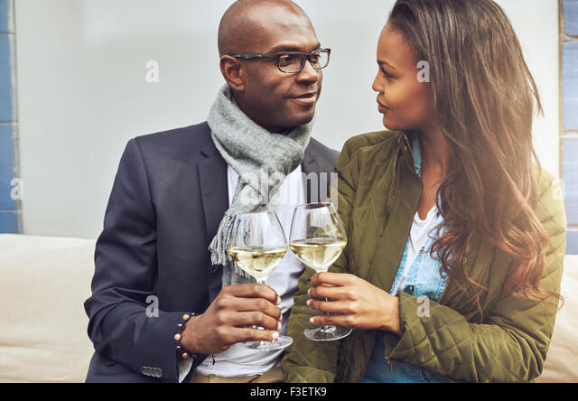 Loving African American couple in a close embrace toasting each other with white wine as they look deeply into each - Stock Image