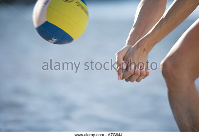 A woman playing beach volleyball - Stock Image