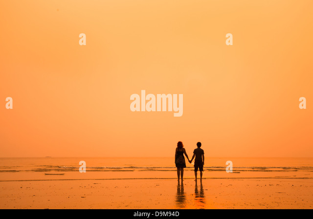 sunset silhouettes of loving couple on the beach - Stock-Bilder