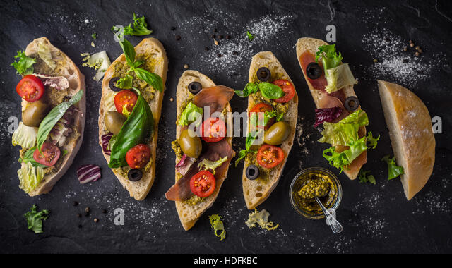 Slices of ciabatta with olives , tomatoes and basil on the black stone table wide screen - Stock Image