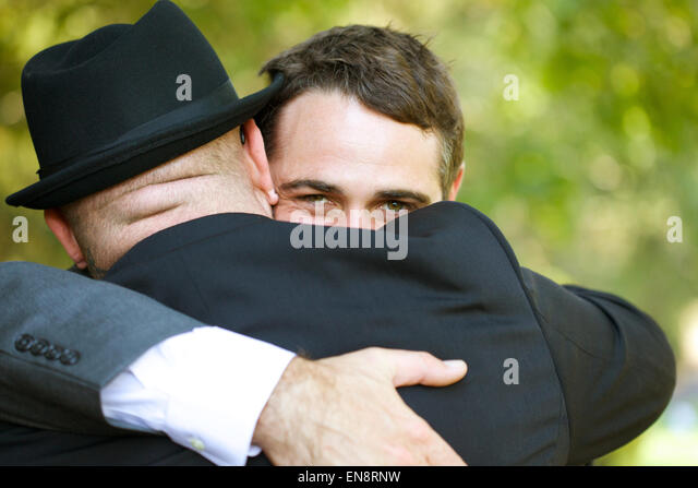 Two men embracing, the one facing the camera makes eye contact with the viewer. - Stock Image