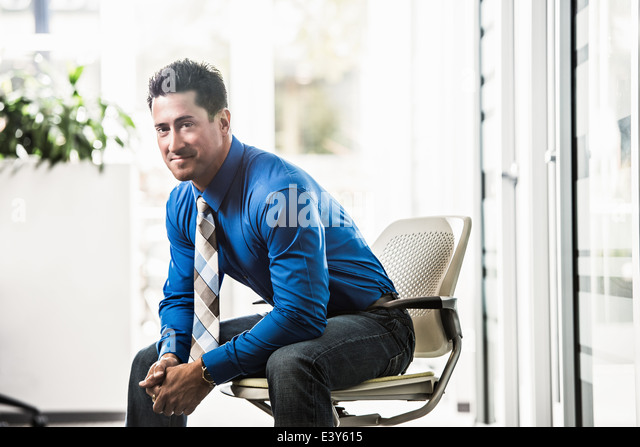 Portrait of mid adult businessman in office - Stock Image