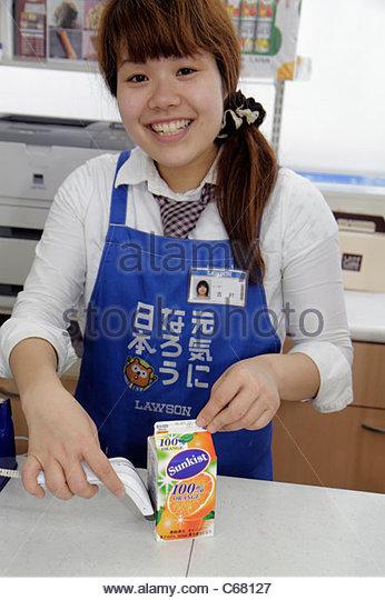 Japan Tokyo Shinjuku Lawson Convenience Store kanji hiragana katakana characters Japanese and English Asian woman - Stock Image