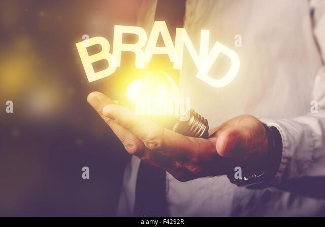 Brand idea concept with businessman holding light bulb, retro toned image, selective focus. - Stock-Bilder