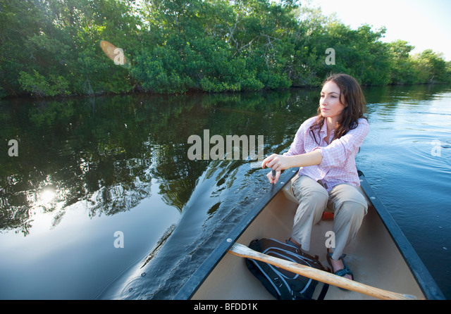 A woman paddles a canoe in Everglades National Park, Florida. - Stock Image