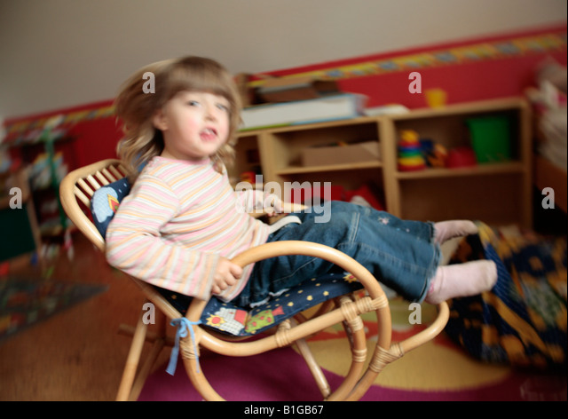 young girl rocking on a rocking chair - Stock Image
