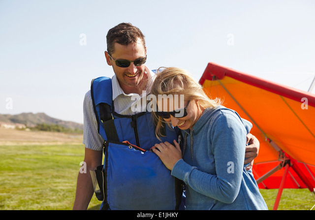 Happy couple, hang glider in background - Stock Image
