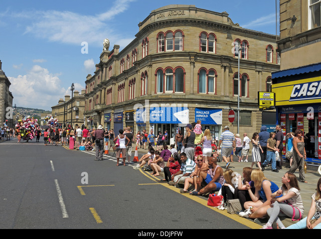 Crowds await costumed dancers from Huddersfield Carnival 2013 African Caribbean parade street party - Stock Image