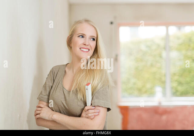 Smiling young woman with pocket rule on construction site - Stock-Bilder