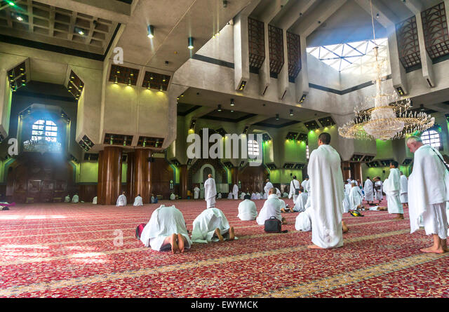 TAN'IM, SAUDI ARABIA - MAR 12 : Muslims pray inside Taneem mosque. - Stock Image