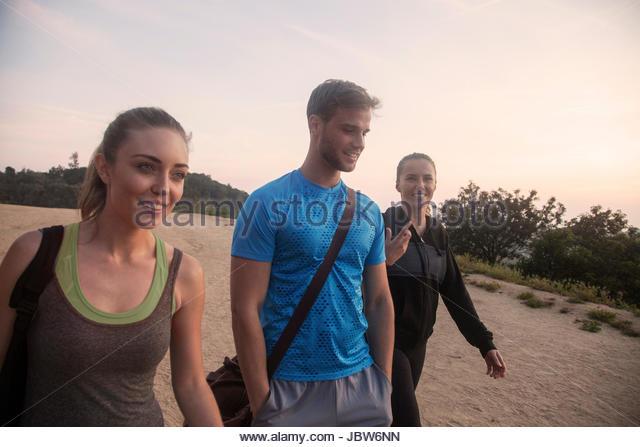 Three friends outdoors, wearing sports clothing, walking along rural road - Stock-Bilder