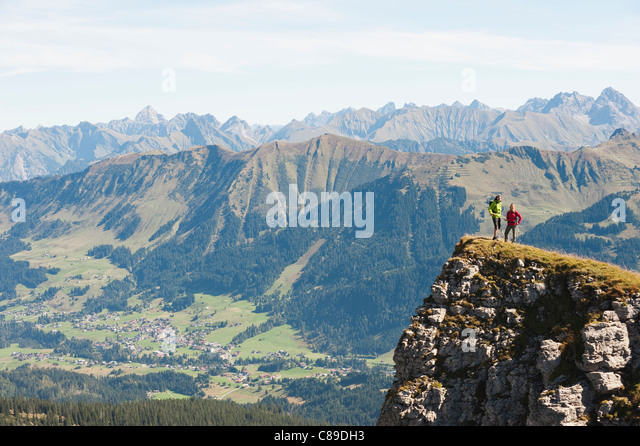 Austria, Kleinwalsertal, Man and woman hiking on edge of cliff - Stock Image
