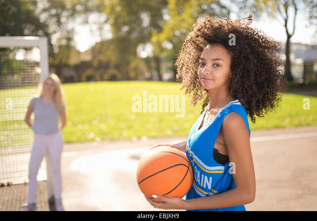 Portrait of young woman holding basketball - Stock Image