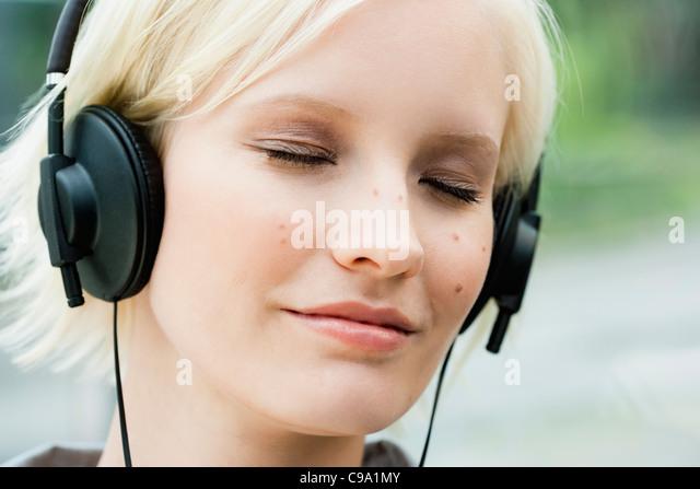 Germany, Bavaria, Munich, Young woman listening music - Stock Image
