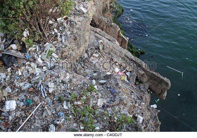 Santo Domingo Dominican Republic Malecon Caribbean Sea seawall trash litter plastic container pollution environment - Stock Image
